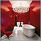 Striking Interior design of scarlet red bathroom with white plank flooring, Laufen sanitary wares & Panton Heart chair.